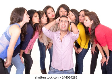 Man going nuts with eight women kissing him