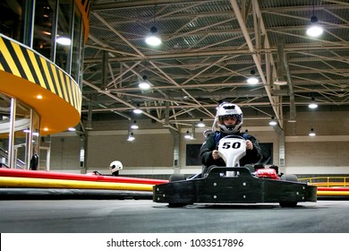 The man is going on the go-kart on karting track. He is wearing a helmet.