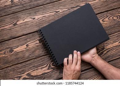 Man is going to open blank black brochure. Closeup shot