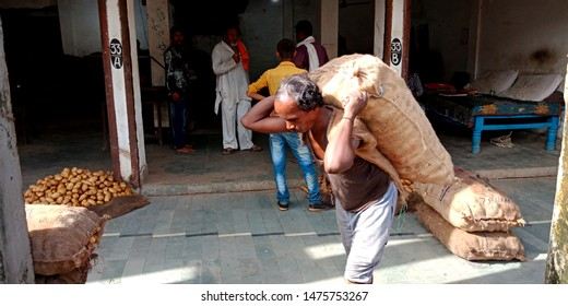 a man is going with potato sack at farmers market district Katni Madhya Pradesh in India shot captured on Aug 2019