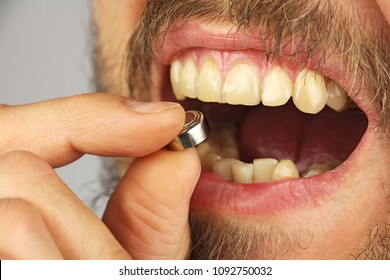 man is going to swallow the battery, holds batery in fingers, side view, closeup