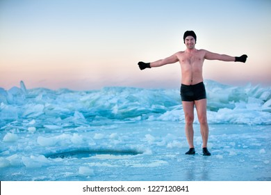 Man is going to swimm in an ice-hole on beautiful winter day