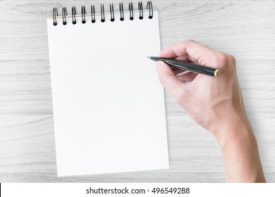 Man is going to write on a notebook.