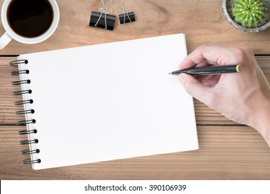 A man is going to write something on a notebook. Top view.