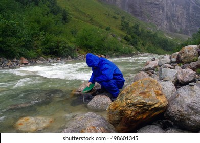 a man gold panning in a river with a sluice box