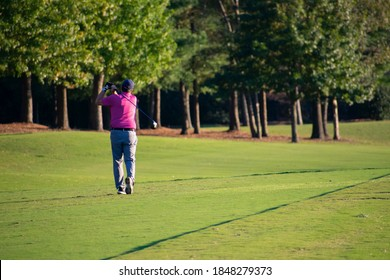 A man golfer swinging and hitting his golfball to the fairway and then the green of the luxury hard and difficult country club golf course.