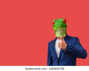 man with googly-eyed frog mask making a like or thumbs-up on red background with copy space