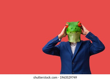 man with googly-eyed frog mask surprised with his hands on his head on red background with copy space