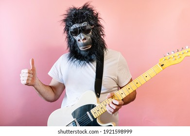 Man with gorilla mask and hanging electric guitar showing his thumb up