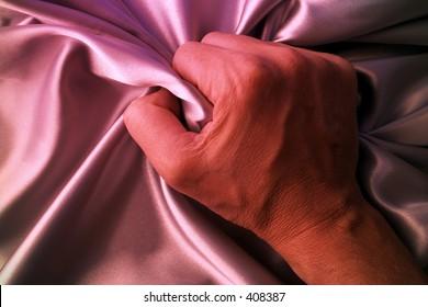 Man grabing satin sheet on the bed.