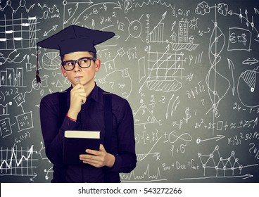 Man in graduation cap with book thinking about education, work life balance planning future standing by info graphics blackboard