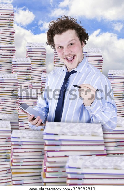 man with graphics tablet among many books