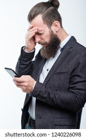 man grasping head and holding phone. failure and emotional reaction to bad news.