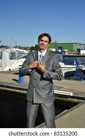 man in a gray business suit straightens his tie, in the background of yachts