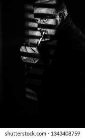 Man with gray hair and beard looking intently with shadows from blinds crossing face, lighting cigarette in film noir style image black & white but with red glow on cigarette end, moody dark low key
