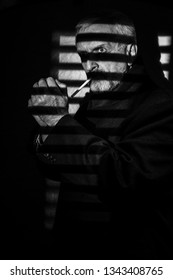 Man with gray hair and beard looking intently with shadows from blinds crossing face, preparing to light a cigarette in film noir style image black & white, dark low key