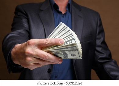 A man in a gray jacket is holding a lot of money in his hand