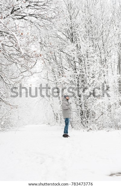 a man in a gray jacket and jeans in a white snow forest, in the winter
