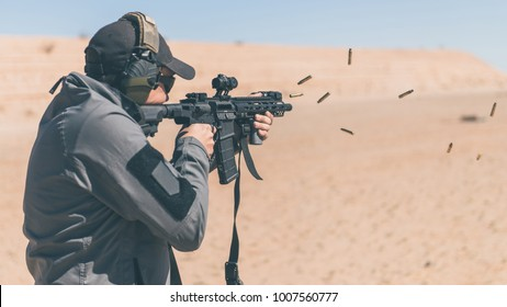 Man with gray jacket shooting black rifle on range in desert shells ejecting angled