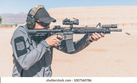 Man with gray jacket shooting black rifle on range in desert shells ejecting profile