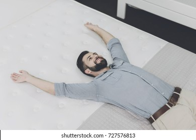 A man in a gray shirt chooses a mattress in a large mattress store. He just decided to lie down on one of them to try it out