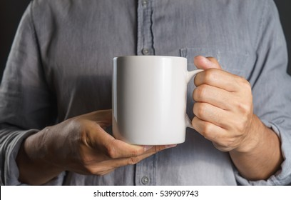 Man With gray shirt holding coffee mug