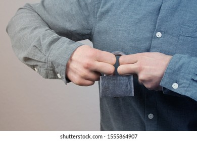 man in a gray shirt holds a closed iron lock in his hands, trying to break it, concept of difficulties, close-up