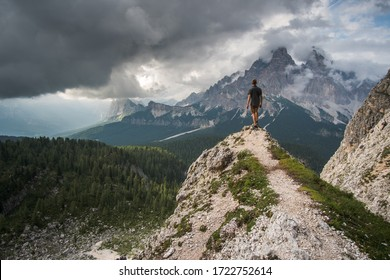 Man in gray shirt standing on steep ridge, when dark clouds are passing by the slopes of the mountains