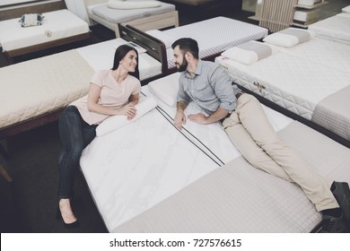 A man in a gray shirt and a woman in a light T-shirt lay on a mattress in the store. They're going to buy a mattress. They lie on it and look at each other