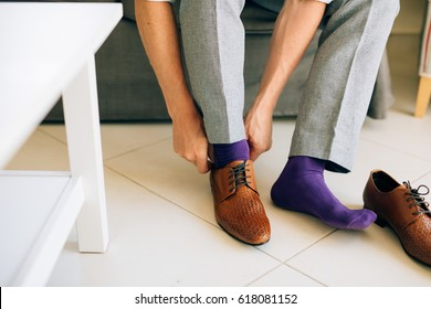 The man in gray slacks and a purple dress socks brown shoes with laces sitting on the couch.