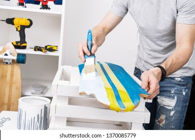 A man in a gray T-shirt is painting a skateboard board in a workshop and listening to music on headphones.