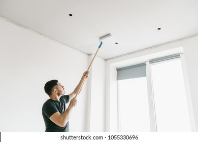 a man in a gray T-shirt with a roller on a long stick paints the ceiling in gray at home. Repair of the premises.