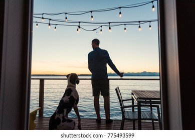 Man and great dane dog enjoying a sunset over sea view with a glass of wine, rear view from window.