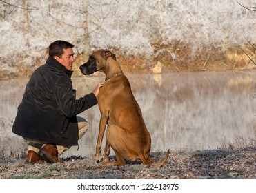 man with great dane near pond