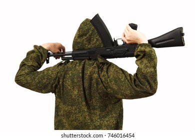 The man in green camouflage clothes and in a mask holds weapon in hand on a white background