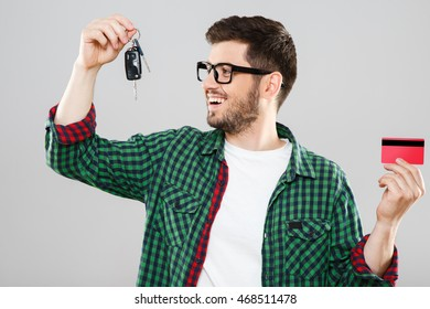 Man in green checked T-shirt and eyeglasses holding car keys in one hand and red credit card in other. Looking at keyes. Waist up. Indoors, studio