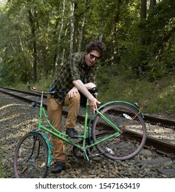 a man with green clothes and a green bike is posing on train tracks in front of a green forest.