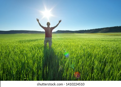 Man in green meadow and sunshine. Conceptual active and  agricultural scene.