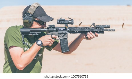Man with green shirt shooting black rifle on range in desert shells ejecting profile