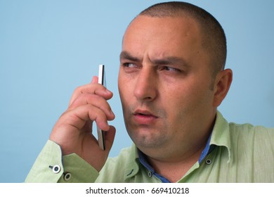 Man in green shirt with a smartphone.
