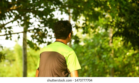 Man in a green t shirt sitting around a place