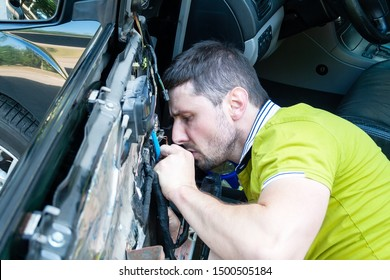 A man in a green t-shirt intently disassembles a car door in order to repair a power window. Car repair at a service station by a qualified worker. Searching for a problem in a faulty car