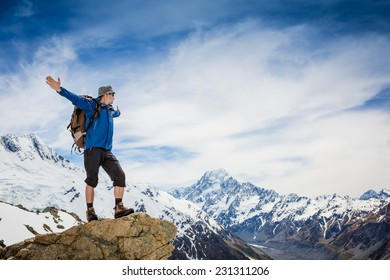 Man greeting amazing nature on the top of mountain. New Zealand