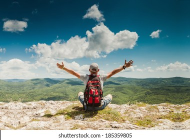 Man greeting amazing rich nature on the top of mountain
