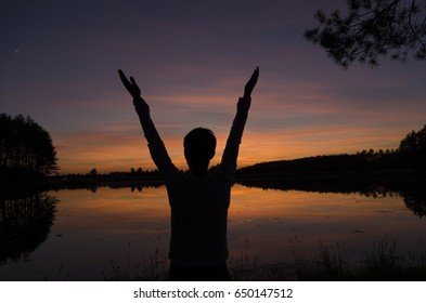 Man greeting sunset standing near the lake and  raises his hands to the sky