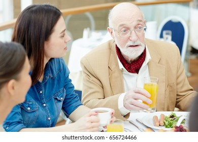 Man with grey beard holding glass of orange juice while talking to his family by breakfast