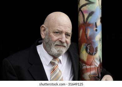 Man with a grey beard hugging the graffiti pole.