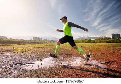 Man with grey beard running on the dirty trail at mountain background in the morning. Healthy lifestyle concept