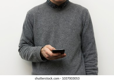 Man in grey crew neck sweater working with phone