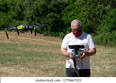 Man with grey hair flying a drone on a field with a tablet and a safety face mask. New normality concept.